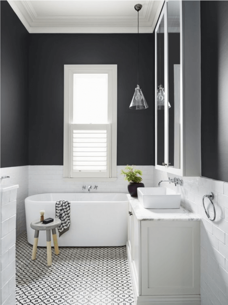 Bathroom design featuring charcoal half walls with stark white tiling and a free standing tub