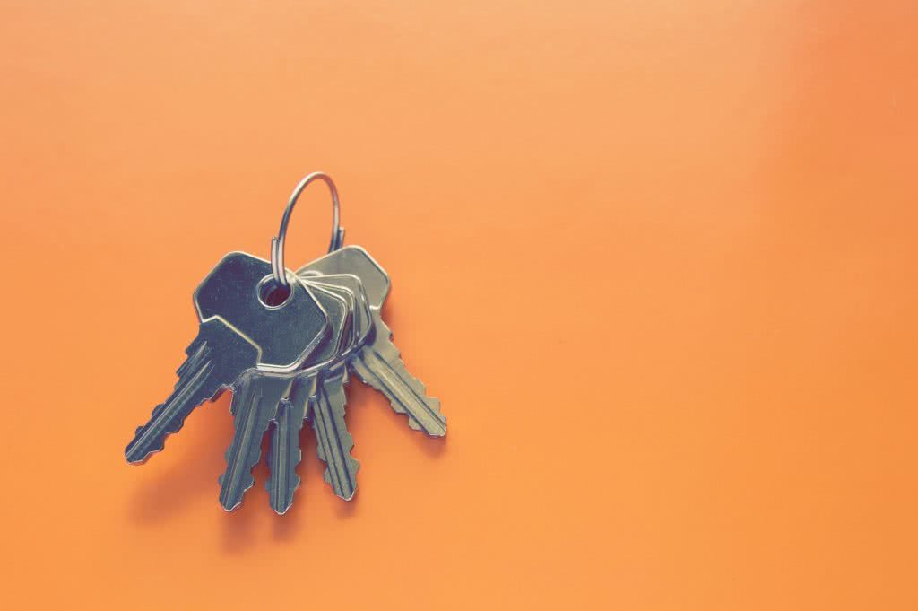 Close-up of set of keys on orange background, goal of creating financial plan