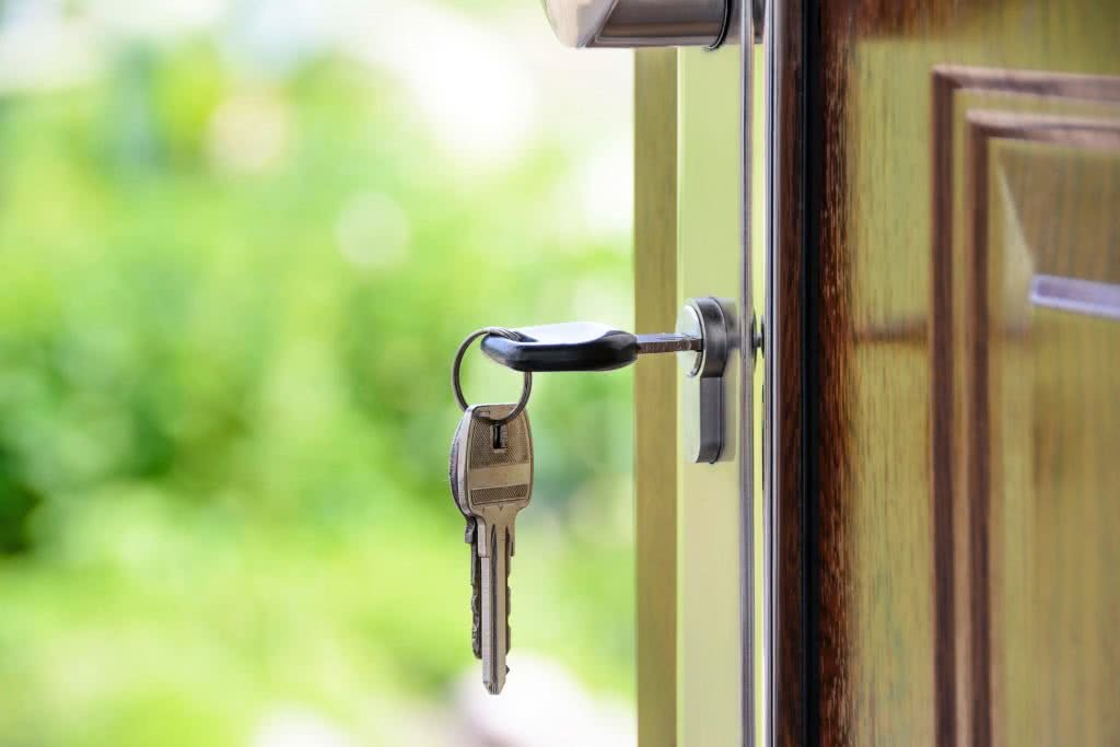 A key in door lock, opening door to investment property