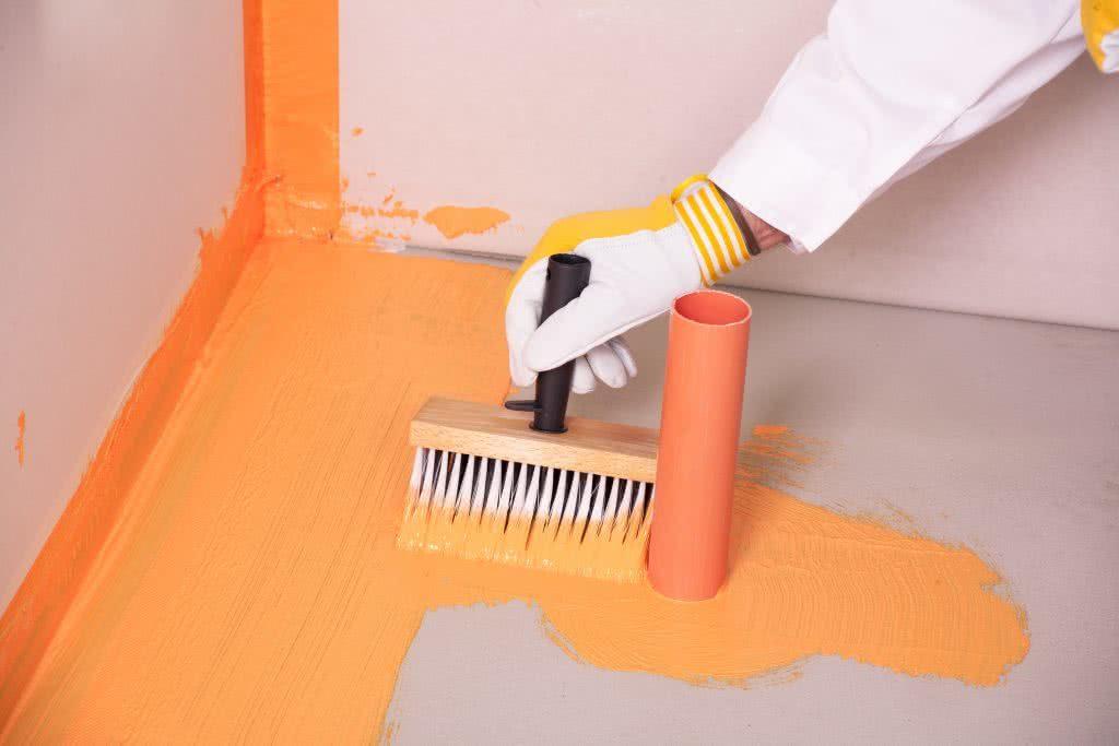Plumber waterproofing bathroom floor during home building
