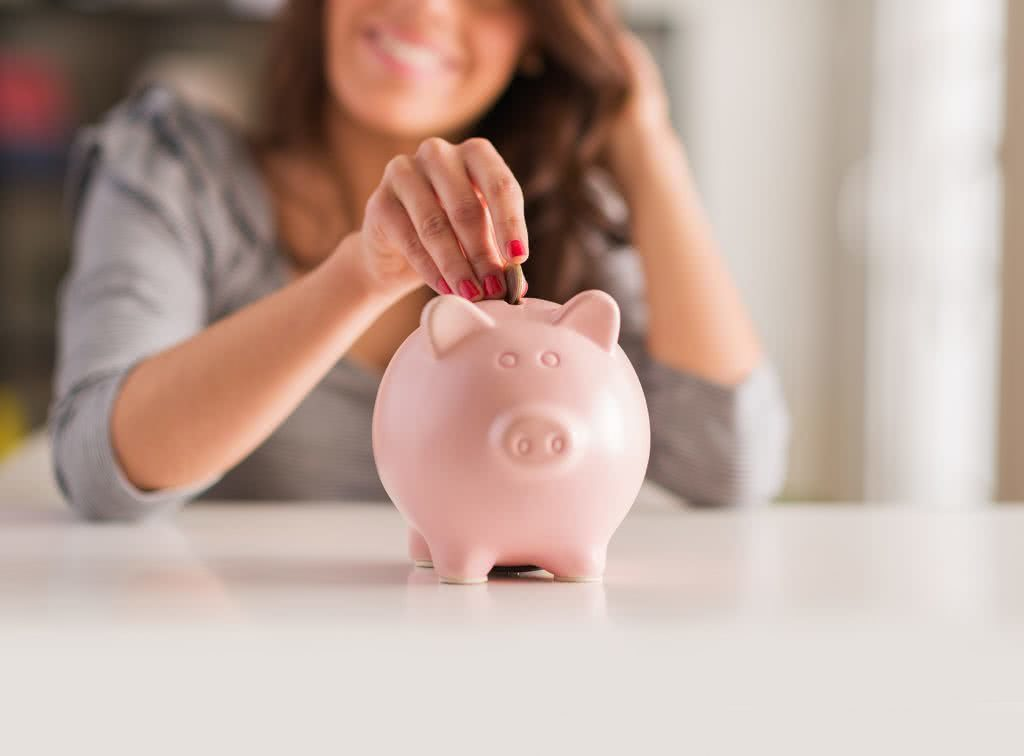 Young woman placing coin into pink piggybank, saving for deposit