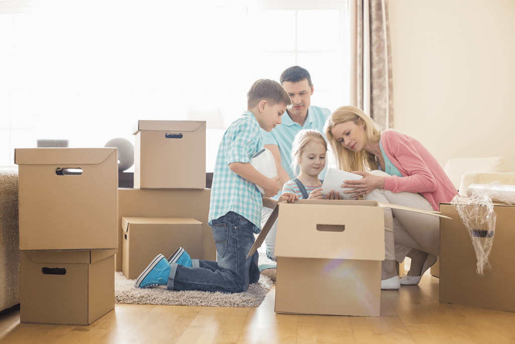 Young family of four unpacking boxes in their new home