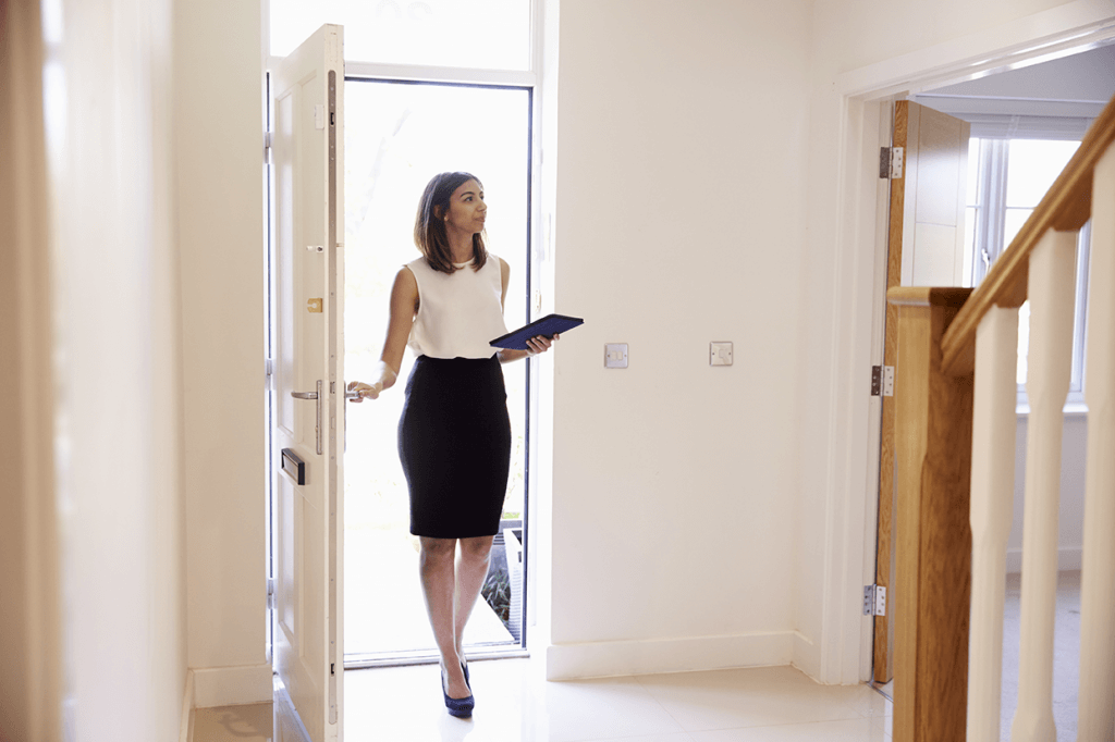 Real estate agent opening front door of property to conduct property valuation